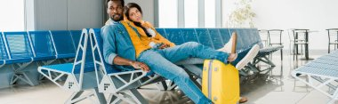 panoramic shot of tired african american couple sitting in departure lounge with suitcase and waiting for flight