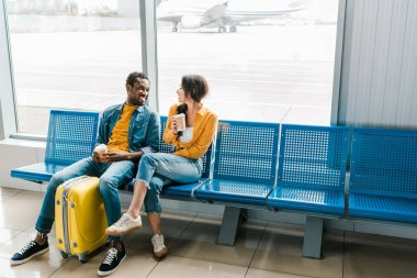 happy african american couple sitting in departure lounge with coffee to go and yellow suitcase