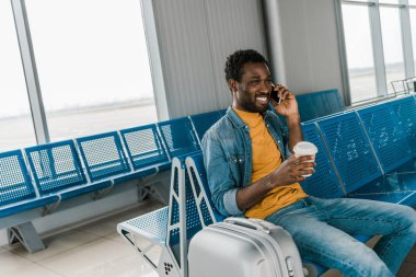 Smiling african american man sitting in departure lounge and talking on smartphone stock vector