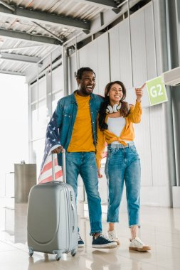 smiling african american couple with american flag and suitcase walking  in departure lounge in airport