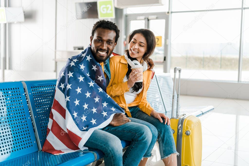 Happy african american couple sitting with american flag and baggage in departure lounge in airport