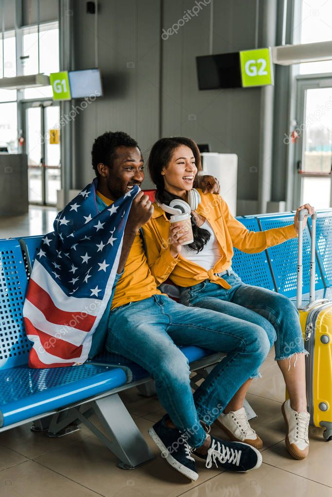 Happy african american couple sitting with american flag and luggage in departure lounge in airport