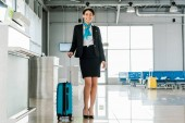 Fotografia smiling african american stewardess standing with suitcase in airport