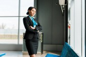 Fotografia african american stewardess standing with crossed arms in airport and looking at window