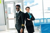 Fotografia smiling african american pilot in sunglasses and stewardess with crossed arms standing together in airport