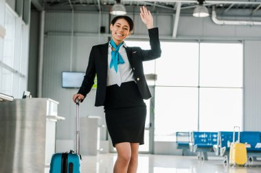 smiling african american stewardess waving hand in airport