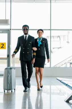 African american pilot and stewardess walking together with baggage in airport stock vector