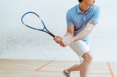 Cropped view of sportsman in blue polo shirt playing squash in sports center
