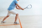 Fotografie Cropped view of sportsman in blue polo shirt playing squash in sports center