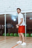 Full length view of sportsman in red shorts playing squash in four-walled court