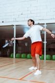 Ganzkörperansicht eines Sportlers in roten Shorts, der Squash auf einem vierwandigen Platz spielt