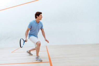 Concentrated sportsman in blue polo shirt playing squash in sports center