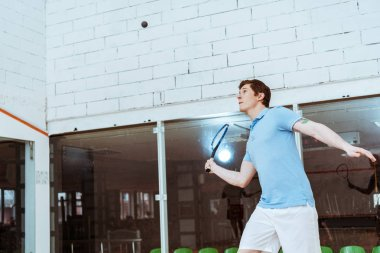 Sportsman in blue polo shirt playing squash in four-walled court