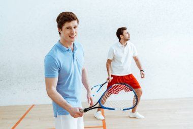 Handsome squash player in blue polo shirt looking at camera