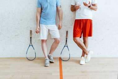 Cropped view of two squash players in shorts standing with crossed legs in four-walled court