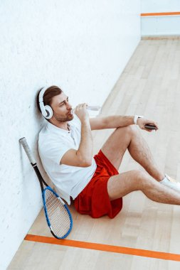 High angle view of squash player listening music in headphones and drinking water