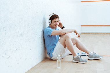 Smiling sportsman sitting on floor and listening music in headphones
