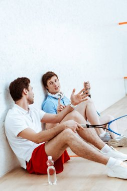 Two squash players talking while sitting on floor in four-walled court