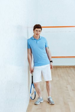 Full length view of squash player in blue polo shirt looking at camera
