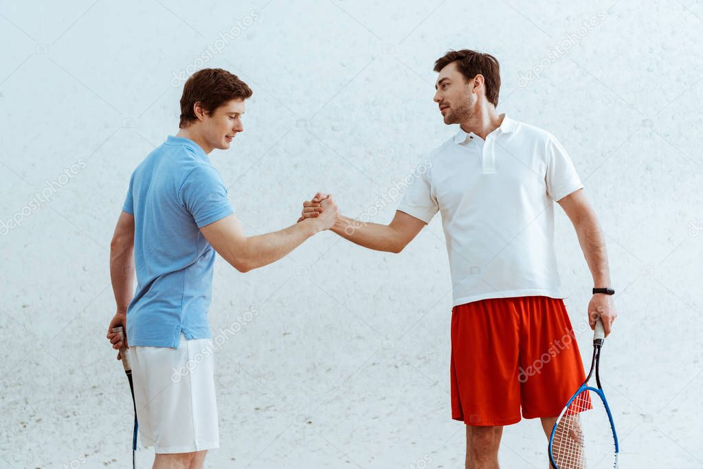 Two squash players with rackets shaking hands and looking at each other