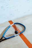 One squash racket and ball on wooden surface