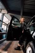 attractive blonde girl standing near black car with open door