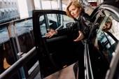 emotional blonde girl  gesturing near black car with open door
