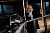 vonzó szőke lány beszél okostelefon és intett a közelben fekete autó