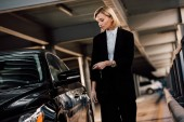 beautiful blonde woman holding key and standing near black automobile in parking