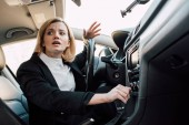 low angle view of emotional blonde woman gesturing while sitting in car
