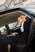 beautiful blonde young woman using laptop while sitting in car