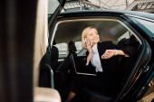 Blick auf eine glückliche Frau, die mit dem Smartphone spricht, während sie mit Laptop im Auto sitzt
