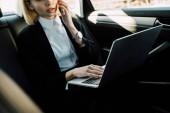 Ausgeschnittene Ansicht einer blonden Frau, die in der Nähe ihres Laptops im Auto mit dem Smartphone spricht