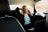smiling blonde woman talking on smartphone near laptop in car