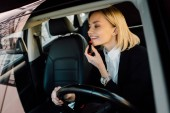cheerful blonde young woman applying lipstick in car