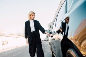 beautiful blonde woman standing near black car in parking