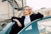 sebevědomá blondýnka v brýlích stojících poblíž černého auta a dotýkala se brýlí
