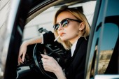 Fotografie blonde woman holding lighter with fire while smoking cigarette in car