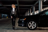 stylish blonde woman walking near black car in parking