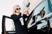 Fényképek veszélyes szőke nő napszemüveg Holding Gun közelében autó