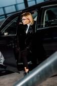 attraktive junge blonde Frau mit Brille sitzt im schwarzen Auto