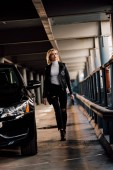 attractive blonde girl walking in parking with key near black automobile
