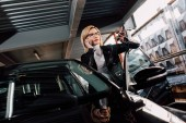 pretty blonde girl in glasses talking on smartphone and gesturing near black car