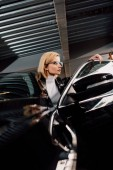 serious and attractive girl in glasses near black car in parking