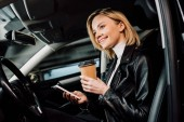 low angle view of cheerful blonde girl holding paper cup and smartphone in car