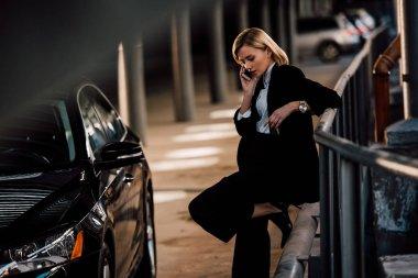 güzel sarışın kız akıllı telefon konuşuyor ve siyah araba yakınında duran