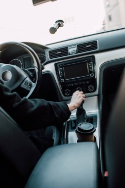 cropped view of woman holding gear shift handle while sitting in car