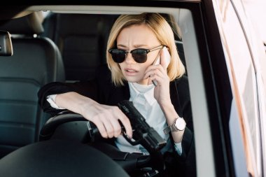 Blonde woman in sunglasses talking on smartphone and holding gun in car stock vector