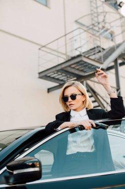 Beautiful woman in sunglasses holding cigarette and gun near automobile stock vector