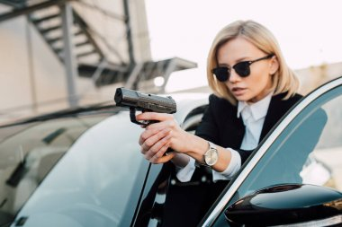 selective focus of serious blonde woman in sunglasses holding gun near black car